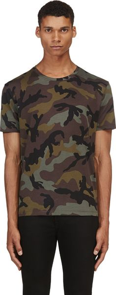 Short sleeve relaxed-fit t-shirt in tones of green, black, and purple. Camouflage pattern throughout. Ribbed crewneck collar. Single gold-tone pyramid stud at nape of neck. Tonal stitching.
