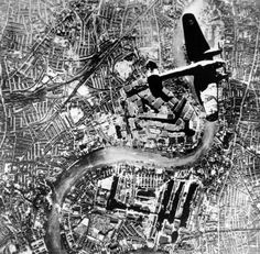 A Nazi Heinkel 111 bomber flies over London during the Battle of Britain in the autumn of 1940 during World War II. The Thames River runs through the center. The Tower Bridge is visible near the plane's left wingtip.