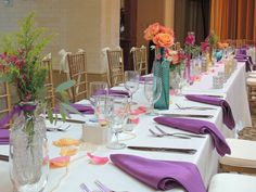 Center Pieces. Wedding. Floral center pieces. Mixed arrangements. Shabby Chic. colored vases. long table arrangements. Solidago filler. coral roses. purple stock. purple sprays.
