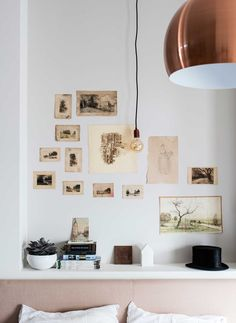 gallery of vintage prints, blush headboard, copper light