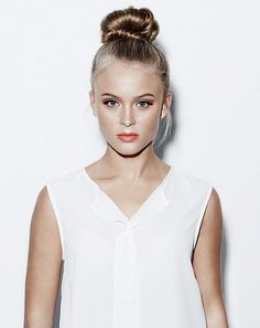 Zara Larsson styles her topknot with a peach lip, gold eyeshadow, and fluttery eyelashes