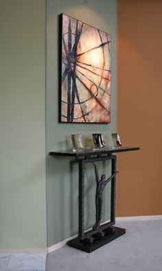 Slim, unique console table, topped with wonderful art, and contrast paint colors, make this small niche memorable.  Vicki Blakeman Interior Design.