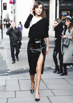 Alexa Chung wearing a two-toned long sleeve sweater tucked into a black patent leather asymmetric zip skirt