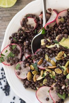 Recipe for lentil, avocado, and radish salad with mint and lime dressing. Garnished with tamari roasted pumpkin seeds. Vegan and gluten-free.