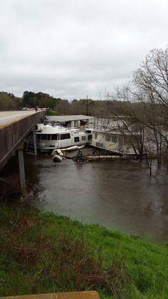 House boats after boat dock broke loose wrecking into bridge