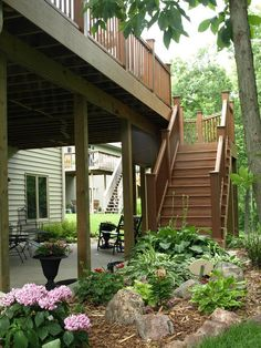 patio under deck with flowerbed and small boulders