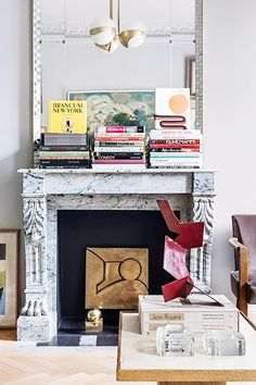 Carved fireplace mantel with stacks of books on Thou Swell @thouswellblog