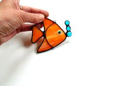 This little fish is so cute! He is made of wispy orange stained glass, and has 3 blue glass air bubbles. His best feature is his eye, complete with eyelashes. He has a nylon cord attached and is ready for hanging. This whimsical little fish will add a bit of charm to any window he hangs in. He can also be used as an ornament. This suncatcher pattern is my own design. © Designs Stained Glass Measures: 3 1/2 long x 3 1/4 high More suncatchers here: http://etsy.me/22pRiu6 Enter my shop here...