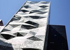 фис в деловом районе Токио Архитекторы из японской студии Amano Design Office разработали коммерческое здание в деловом районе Токио Гинза, которое украшает граненый алюминиевый фасад, напоминающий смятую обертку сладкой конфеты.