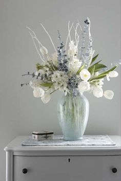 A pale winter floral arrangement is created with green eucalyptus and dried pods sprayed soft white, white tulips, white hyacinths and white branches. Design by Karin Lidbeck Brent, Photography by Michael Partenio
