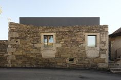 A stone ruins home mixed with modern architecture.