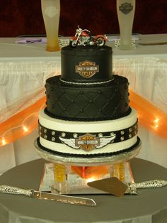 """Tommy and Shannon - 6-10-12"""" tiers stacked.  All buttercream.  Harley Davidson logos are image transfers glued to gumpaste plaques with piping gel then attached to cake.  Bottom tier is wrapped with a ladies belt from Walmart.  :)   Hard to see, but the top tier has piping to look like the stitching on a motorcycle seat.  This one was tons of fun to do!  Thanks to Edna and Jeep_girl for help with the gumpaste questions!"""