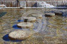 Round stepping stones in front of a waterfall