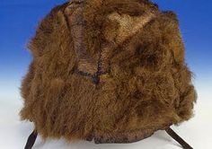 Ötzi's hemispherical bearskin cap, which was found near the mummy's head.  It was made of several hide strips stitched together.  On the lower edge, two leather straps were attached which were tied under the chin to keep the cap in place. Both chinstraps were already torn before Ötzi's death.