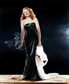 Rita Hayworth as Gilda in her famous black stain sheath gown in color designed by Jean Louis in 1946.