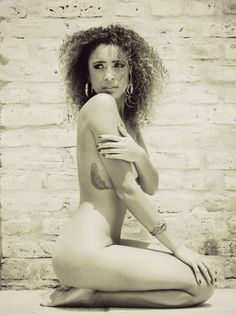 Photo shoot of a nude girl . Curly hair . Sensual . Afro . Feather tattoo . Wall