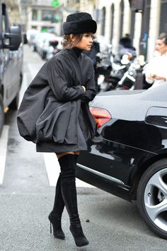 Mira in knee high boots and a big black coat in Paris...