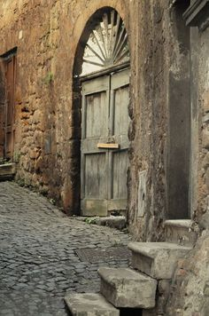 A beautiful old door in a dilapidated cobbled street. I don't know where this is in the world but I want to explore this town!