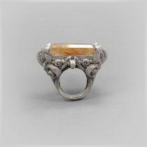Großer verschnörkelter Ring, in dunklem Silber, feenhaft wirkend, mit großem Quarz, von leuchtenden Rutilen durchzogen.