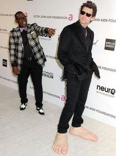 Randy Jackson points at Jim Carrey as he arrives at Elton John's party wearing large feet