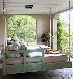 Hanging loungers are suspended on the sleeping porch at a Northern California home by designer Suzanne Rheinstein and architect Ken Linsteadt; the pillows and throws are by Dash & Albert   archdigest.com
