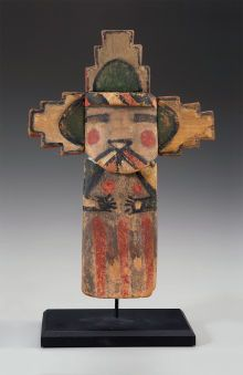 A HOPI COTTONWOOD KACHINA DOLL : c. 1890  representing Salako Mana, with flat body painted in dark gray with red stripes, surmounted by a face mask, featuring rectangular eyes, circles on the cheeks, and a rainbow mouth, with terraced tableta at top, and Heye Foundation accession number 9/925 painted on the back, metal stand
