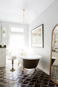 Vintage interior design The gorgeous vintage clawfoot tub was a Craigslist find, which Rosa painted matte black on the outside and reglazed on the inside. It's a stunning find! And the Marc Royce piece above it adds even more luxury.