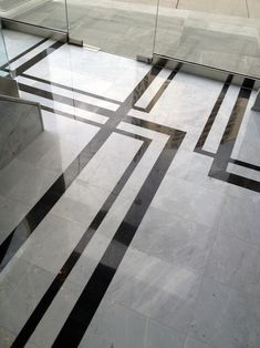 Strikingly contrasting marble creates a floor pattern that's not the typical boarder and works well with the asymmetrical layout in the space.