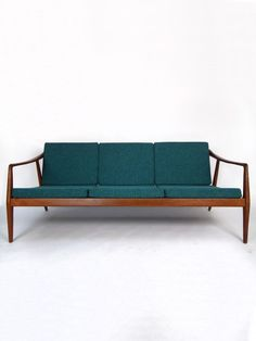 Mid-century teak wood threeseater sofa - with a bleu green upholstery.  A wonderful match