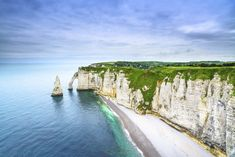 "Étretat in Normandy, France. Étretat is best known for its cliffs, including three natural arches and the pointed ""needle"". These cliffs and the associated resort beach attracted artists including Eugène Boudin, Gustave Courbet and Claude Monet,"