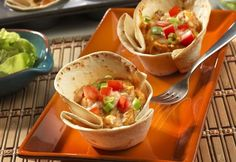 """""""These individual chicken enchilada cups will absolutely thrill your family. Cooked chicken, picante sauce, sour cream, cream of chicken soup and Monterey Jack cheese combine to make a tasty filling for warm flour tortilla cups. Pop them in the oven for 20 minutes and you've got a creative, delicious meal ideathat can't be beat."""""""