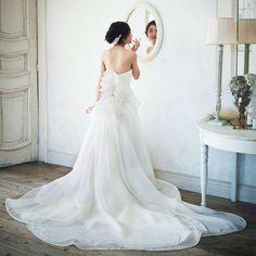 """小柄花嫁ドレス③背後からの視線も上にあげてくれる""""華やかバックスタイル""""  バージンロードを歩くとき、キャンドルサービスのとき…、花嫁ドレスは後ろ姿が目立ちますよね。背中の中央あたりから大ぶりのバック飾りがあしらわれたドレスならゲストの視線も上に集中し、すらりとしたボディラインの印象にしてくれます。  シルクサテンオーガンジーを立体的なドレープで構成した「レフェ クチュール」のドレスは、バックスタイルの華やかさが特徴です。背中から流れるようなエレガントなトレーンが小柄花嫁さんに品のよさを授けてくれるでしょう。"""