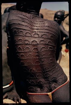 Welts, scars of beauty, pattern the entire back of a Nuba woman in Sudan, 1966.Photograph by Horst Luz, National Geographic