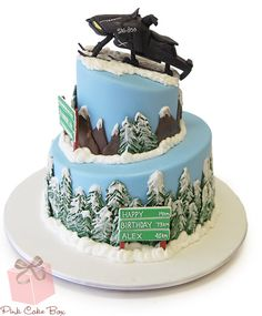 This two tier topsy turvy cake is covered in sky blue fondant and drifts of buttercream snow to represent a snowy Canadian mountain scene. (The birthday bo