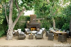 Sophisticated Gray. Designer Tobi Tobin completely revamped the backyard of her Hollywood Hills farmhouse. She used brick from an old patio for the new fireplace and created a terrace from sand mixed with granite. A candlelit chandelier can be raised and lowered by a rope pulley rigged to a tree. It casts a soft glow over Restoration Hardware's Gun Barrel Salvaged Wood dining table and all-weather wicker from World Market.