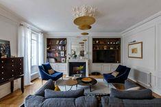 Paris style living #moldings #white #walls #livingroom #paris #flat #blue #chair #shelves