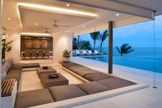 Modern living room with huge sectional sofa and floor-to-ceiling picture windows.