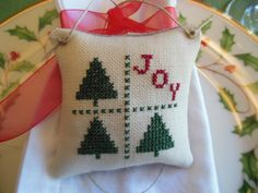 This adorable cross stitch ornament has so many uses. Perhaps you would like your hostess gift to stand out from all others. Simply tie this keepsake to your bottle of wine and your hostess will remember your thoughtfulness. Or your gift basket....or incorporate it in the bow on your package for a loved one. This cross stitch is on linen using two threads over two linen threads. The backing is also linen and a cord tie is attached if you choose to hang. It is lightly stuffed. Measuremen...