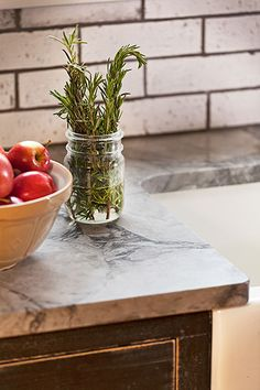 """Granite countertops, """"leathered"""" for a matte finish, and subway tiles with black grout add a rustic, comfy touch to this farmhouse kitchen."""