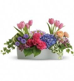 A Spring Arrangement, full of tulips, hyrdrangia, roses and more.  Great for a table centerpiece to bring a little spring into your home.  We deliver.