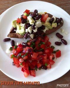 Gepofte zoete aardappel gevuld met kidneybonen, avocado en feta. Erbij tomatensalsa.