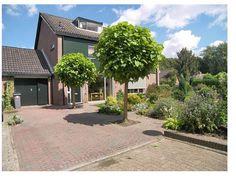 De voorzijde van Lijsterhof 4, met een brede oprijlaan en tuin.