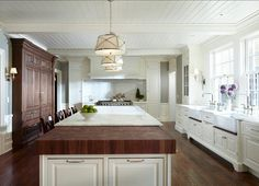 Kitchen with large island with marble and butcher block countertop. The butcher block is made of walnut. This kitchen also feautures beadboard ceilings.