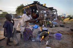 South Sudan | A mother cooks dinner for her kids in Juba. - Found via Buzzfeed