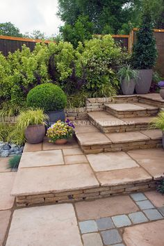Tiered patio with mixed paving materials. Design by Geoff Whiten | Plant & Flower Stock Photography: GardenPhotos.com