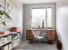 I love the vibe of this cozy workspace. The botanical illustration and the String shelf with pink and terracotta details go so perfectly well together with the vintage desk. The light grey walls give