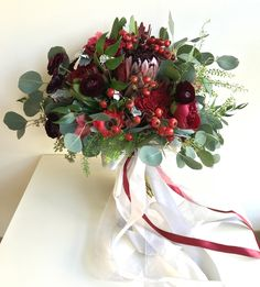 Red textures of ranunculus, anemones, red peonies and Queen protea