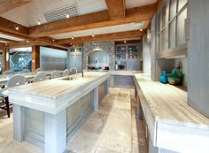 Ocean blue vein cut travertine ties together the look and feel of expansive kitchen. Exposed beams, track lighting, frosted glass cabinets and a range hood hidden by stone completes this ultra modern look #connecticutstone {Credit: RMB Designs Inc.}