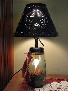 Bring soft light to a room in your home with our Mason Ball Jar Lamp with Metal Shade! https://www.primitivestarquiltshop.com/search?type=product&q=mason+jar+lamp+with+metal+shade #primitivecountryhomedecor