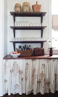 A charming floral curtain (hung on a rod with hooks) hides the dishwasher, making the space seem more traditional and old fashioned. Simple open shelves, old wine casks and a wicker basket holding condiments also keep with the casual, unfitted tone of the kitchen.